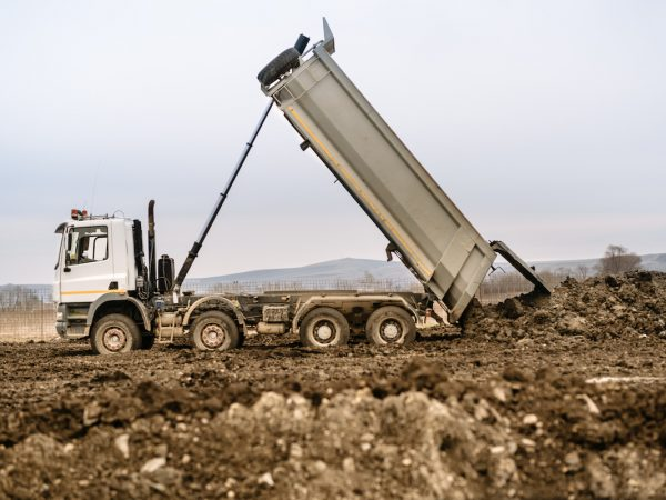 Industrial dumper truck un loading gravel and earth at highway construction site
